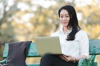 Woman sitting on park bench working remotley with Microsoft 365.